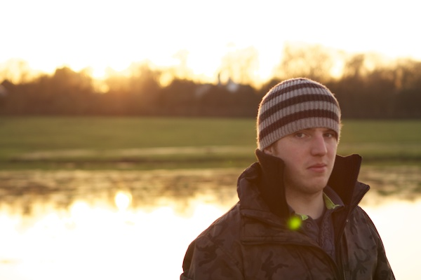 portrait of a man in a hat and coat in the sunset