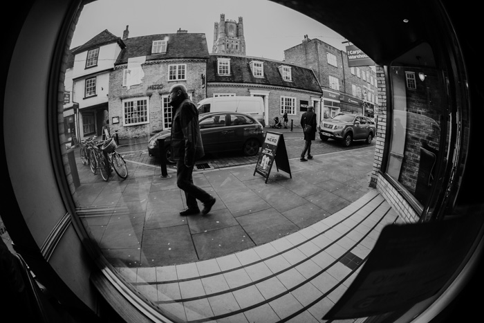 A black and white image of a street scene, shot using ultra Wide Angle focal length