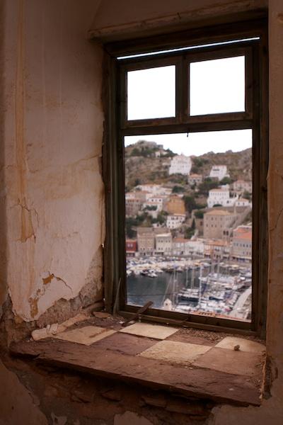 Foto de un puerto griego enmarcado por una ventana vieja