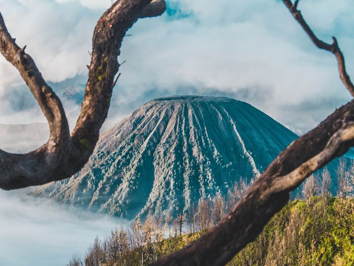 Photo of a volcano with branches framing the foreground