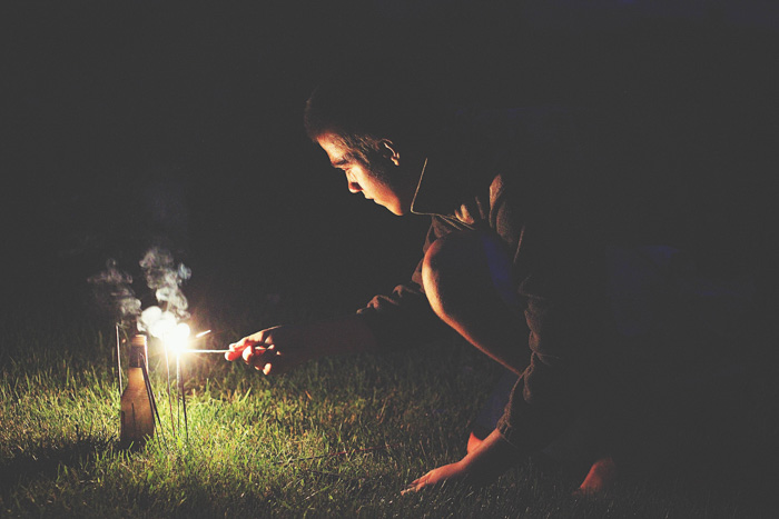 Atmospheric night portrait of a man lighting sparklers outdoors