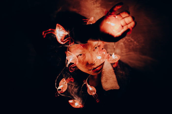 Mysterious and atmospheric low light photography portrait of a girl holding fairy lights