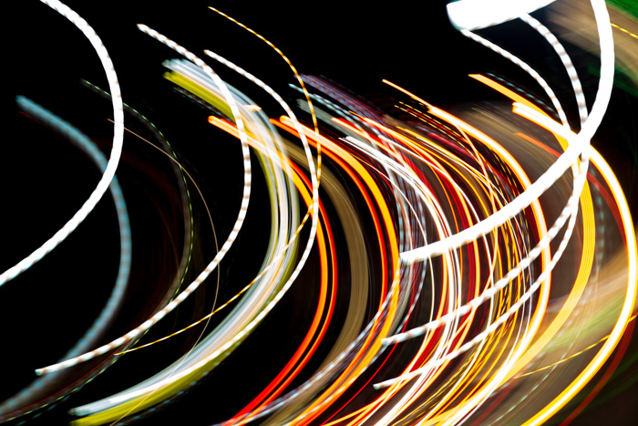 Coloured strands of light against a black background