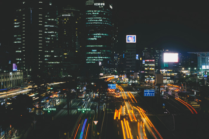A busy cityscape with streaming light trails of cars whizzing by tall buildings at night