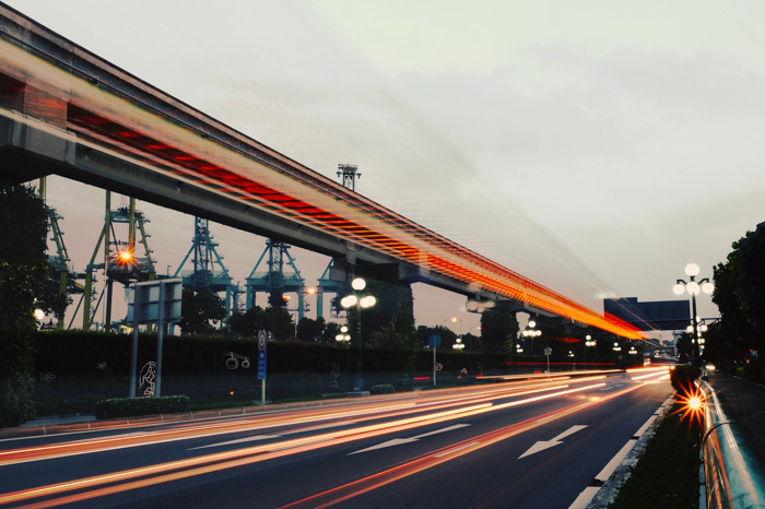 A motorway in the low light of evening with streaming light trails of cars whizzing by