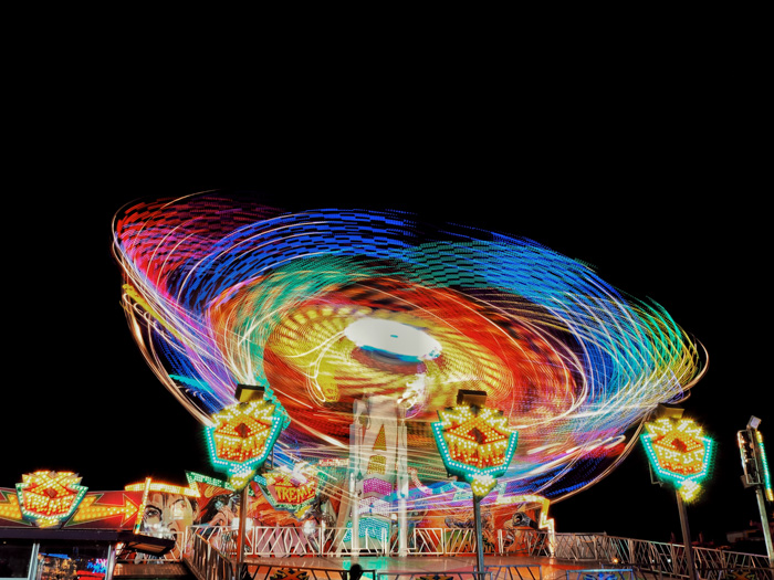Majestic shot of the colourful lights of an amusement park ride at night