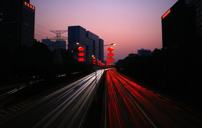 A low light photography cityscape with streaming light trails of cars whizzing by tall buildings at night