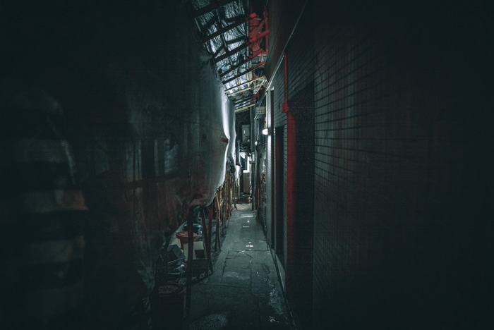 Atmospheric low light photography shot of an industrial alleyway