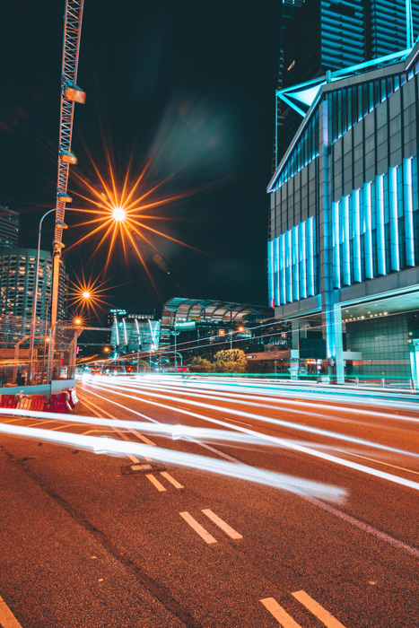 A cityscape with streaming light trails of cars whizzing by tall buildings