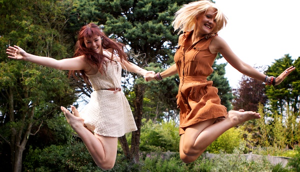 Photo of two young women jumping while holding hands