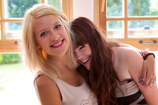 Photo of two young women one hugging the other who is laughing