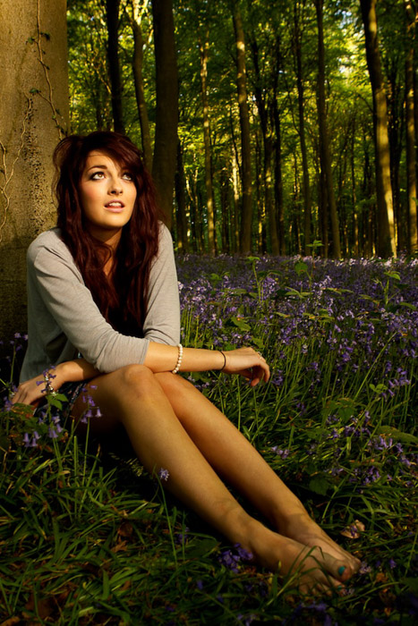 An out door natural light portraits of a femal model sitting under a tree