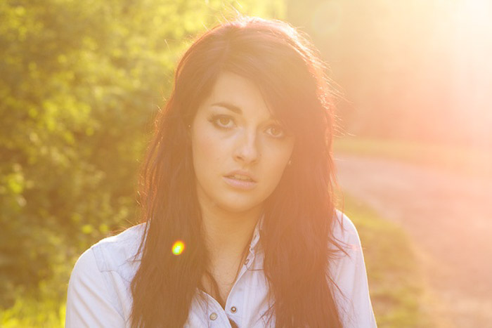 Atmospheric outdoor portrait photography close up of a female model shot with natural light and featuring artistic lens flare