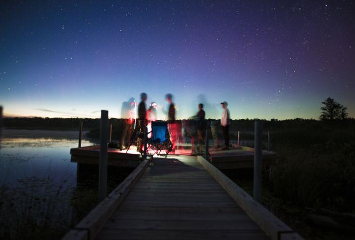 foto de un grupo de personas en un muelle con flash de sincronización lenta