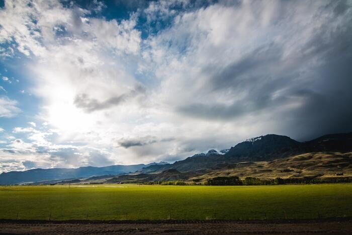Photo of a green field with mountains in the back in sunny weather