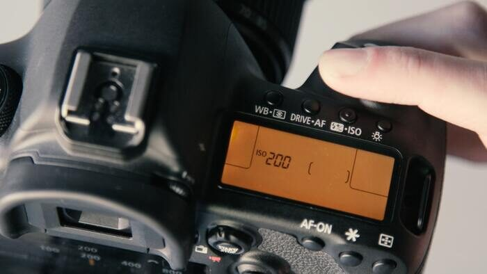 A close up of changing camera ISO settings on a DSLR