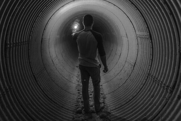 Black and white photo of a guy in a tunnel