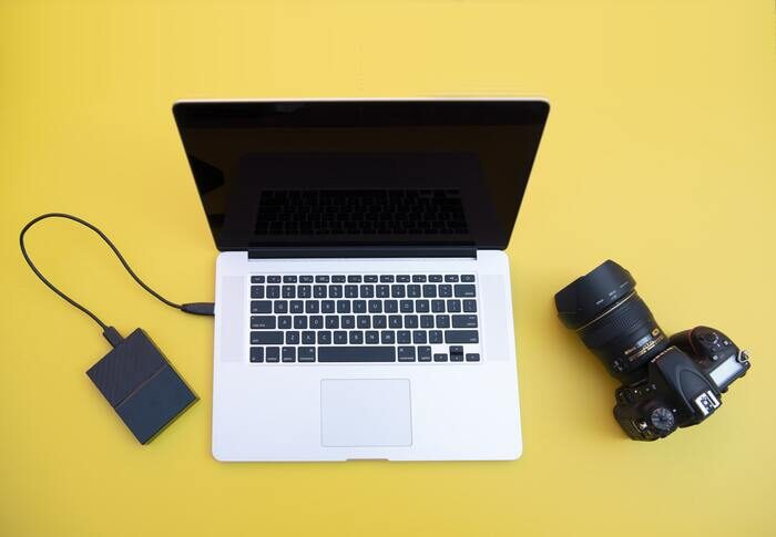 Photo of a laptop, a camera and a hard drive