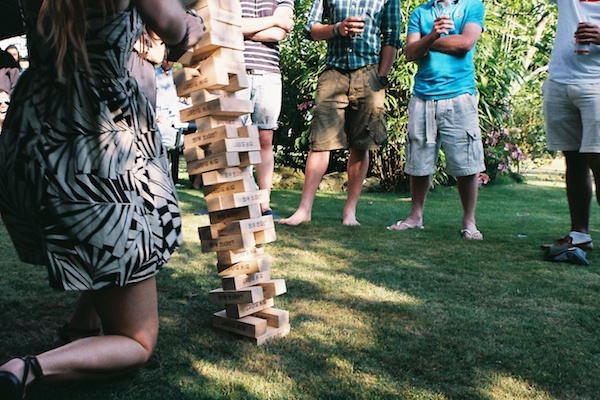 Photo of people standing around a girl playing jenga but you can't see their eyes