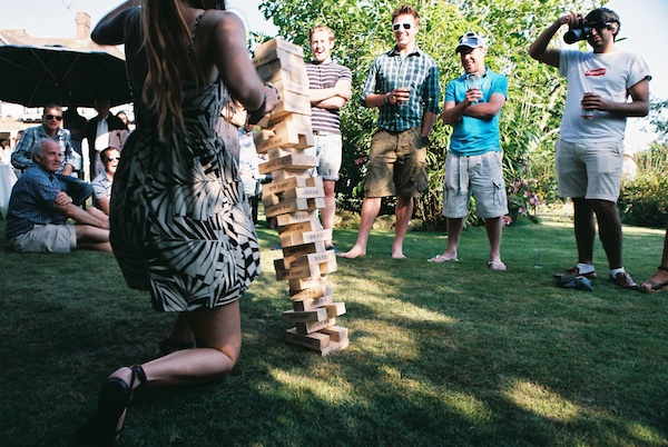 Photo of people looking at a girl playing jenga and visual weight of composition being shifted to her by everyone's eyes directed at her