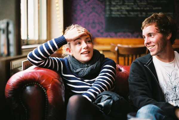 Photo of a young woman sitting on a leather couch and a young man sitting next to her and looking at her