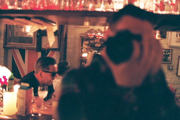 Unfocused photo of a person taking a photo in a mirror in a pub