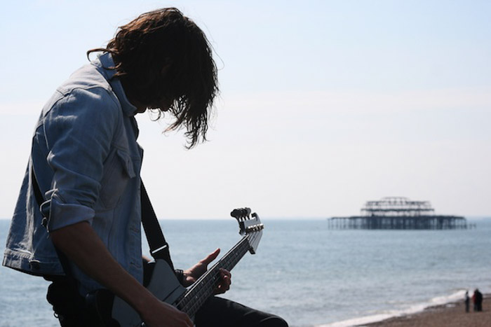 A man playing guitar by the sea, shot without focusing on balance in photography