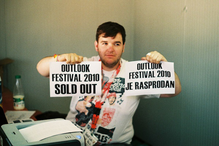 A man holding up two printed signs announcing a festival is sold out - photography balance