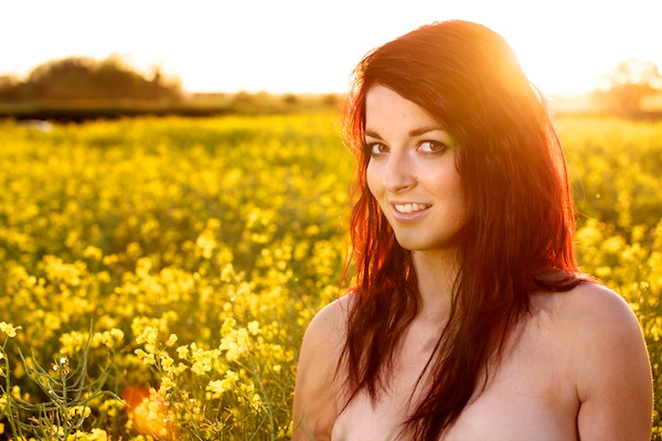 Photo of a young woman in the field of yellow flowers demonstrating editing with contrast