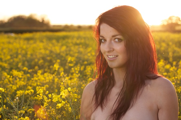 Photo of a young woman in the field of yellow flowers demonstrating editing with exposure
