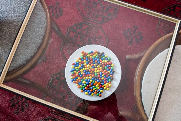 A pane of glass sits above a bowl of m&ms