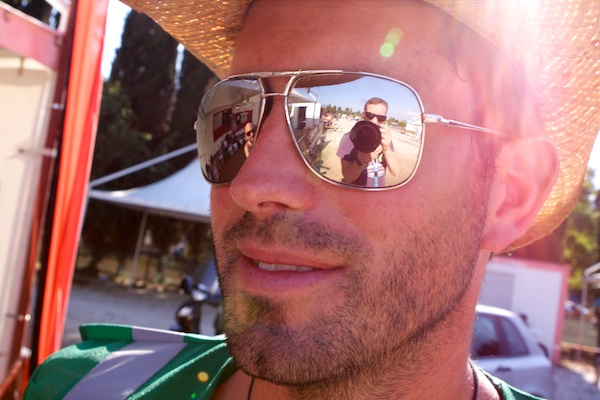 A man in a straw hat reflecting the photographer in his sunglasses