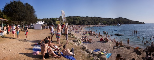 A sandy beach with many people on the sand walking or laying down and some in the water
