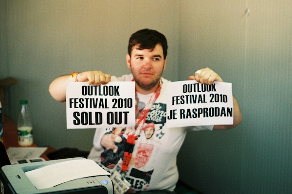 An overweight man holding up two pieces of paper saying: Outlook Festival 2010 sold out