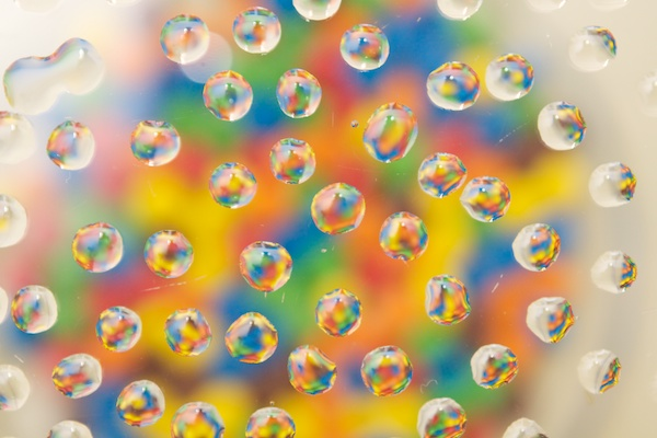 A colorful image of waterdrops in front of brightly colored sweets