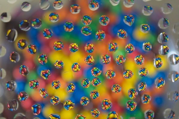 A cool water drop photo arrangement with circles of brightly colored sweets with droplets on a bokeh background