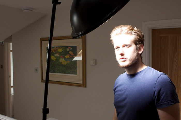 A male model posing for a photo, with low key lighting setup