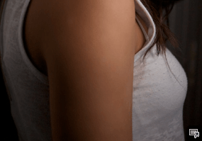 The shoulder of a women in a white tank top