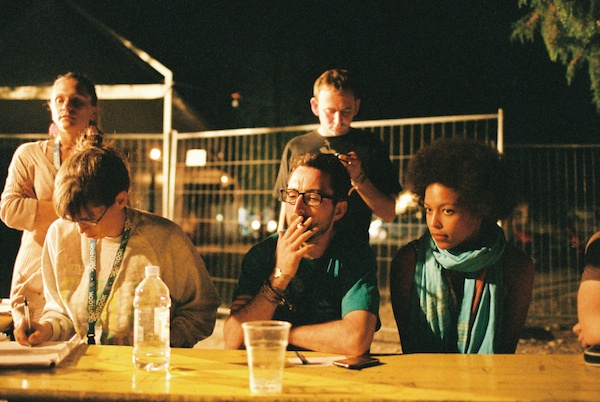 Photo of several people sitting outside in the dark