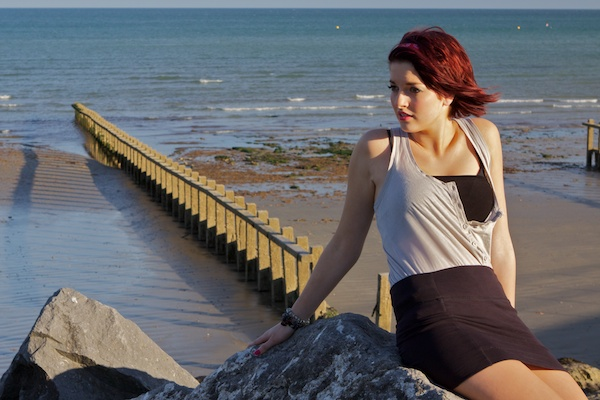 Photo of a young woman sitting on a rock on a beach looking away from the camera
