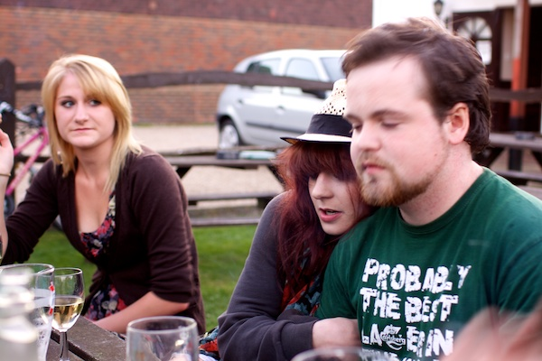 Photo of a couple and a young woman looking at them