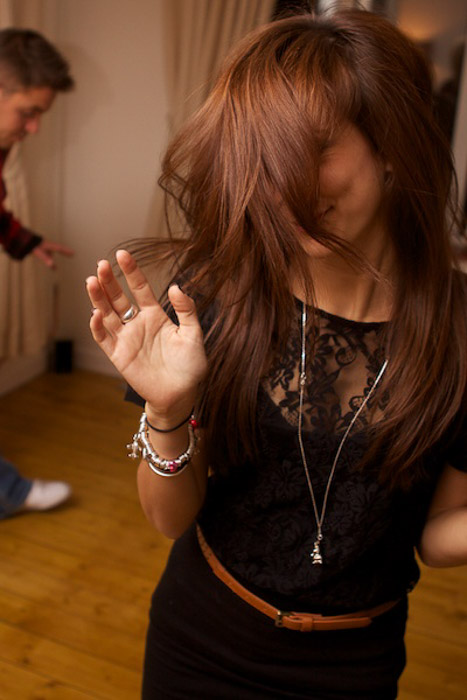 A brown haired female dancing indoors - party photography tips