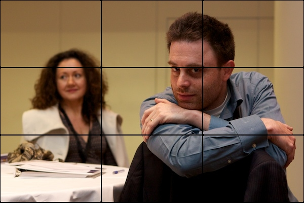 A picture of a man and woman with the man being in focus. The picture is divided up into rectangles.
