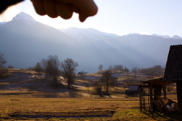 a hand blocking the sun with slovenian mountains in the background