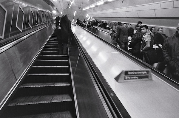 People riding the escalators in London - black and white street photography