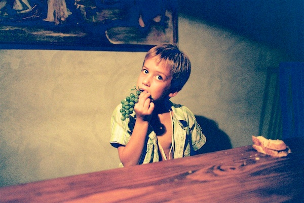 A child eating grapes by a wooden table - find models for free portrait shots