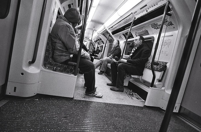 A black and white image of people on a subway - shoot from the hip photography