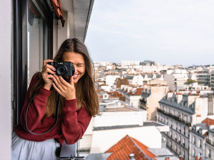 Woman on a balcony taking a photo as part of a 30 day photo challenge