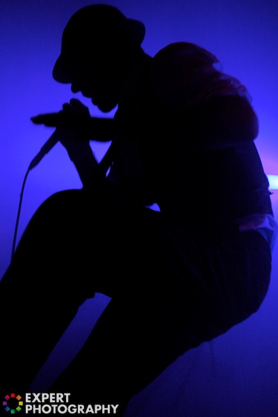 The black silhouette of a singer in a concert with a purple background