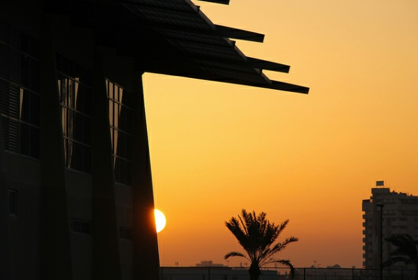 A sunset seen behind the silhouette of a building